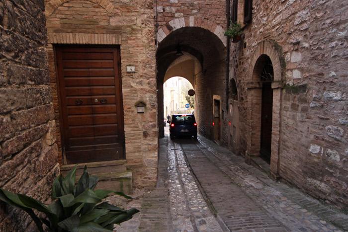 Carro passando por um portal medieval na cidade de Spello, na Umbria