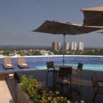 Cadeiras com sombrinha na mesa, piscina no terraço, vista para outros prédios