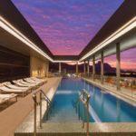 Anoitecendo, piscina com cadeiras de esteira, céu aberto