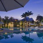 Anoitecendo, piscina com coueiros, barraca de sol