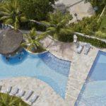 Visto de cima, piscinas, barracas de sol e árvores e arbustos