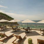 Terraço com cadeiras de esteiras, barracas de sol, vista para o mar