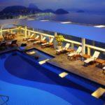 Anoitecendo, psicina no terraço com vista para a praia, visto de cima